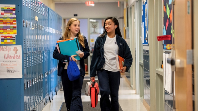 Two middle school students walk down the hall